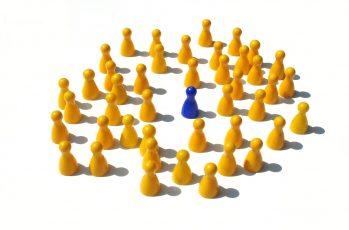 viele gelbe Pöppel und in der Mitte ein einzelner blauer Pöpel