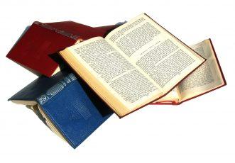 Vier aufgeschlagene Bücher auf einem Haufen